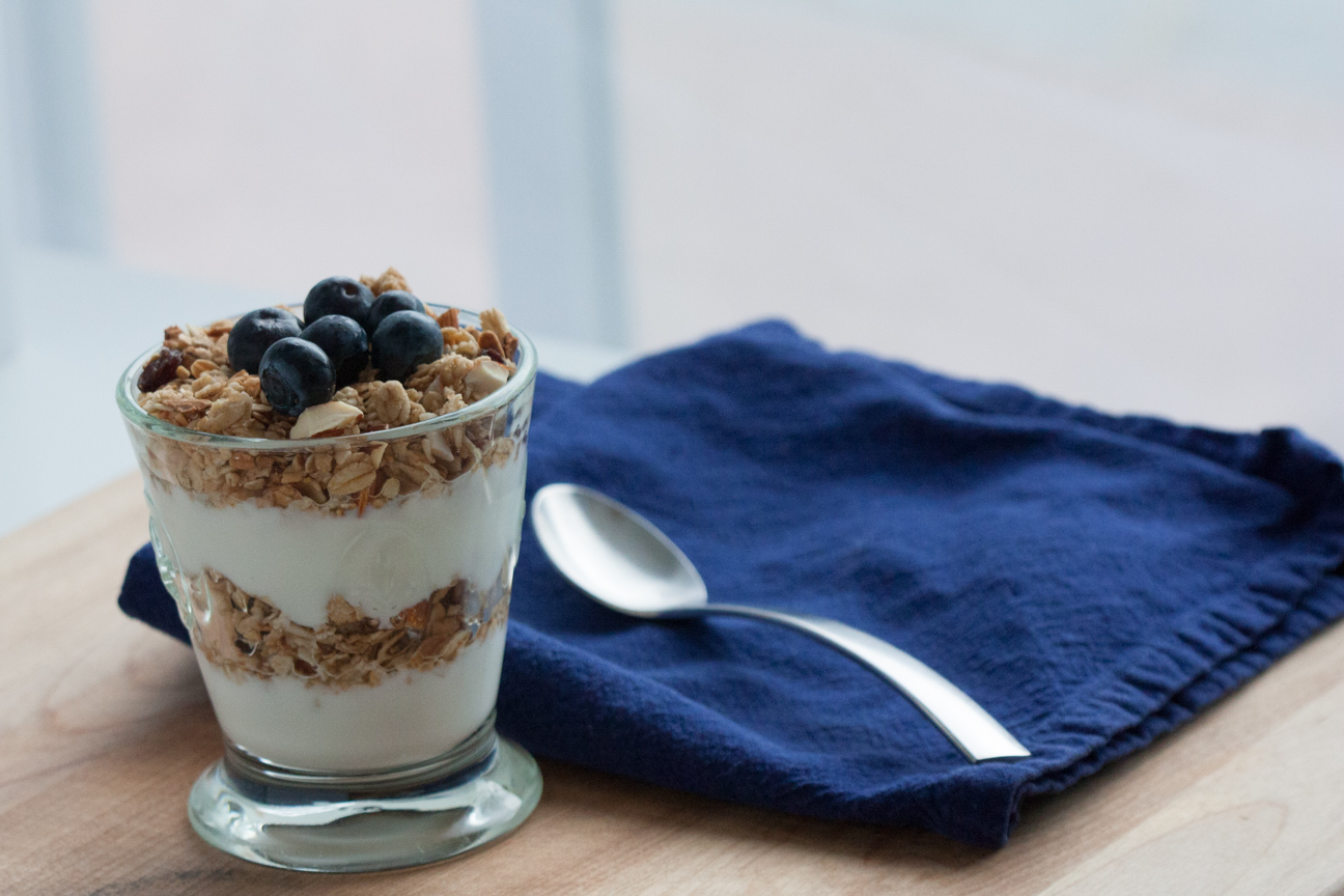 granola and yogurt in glass with blue napkin