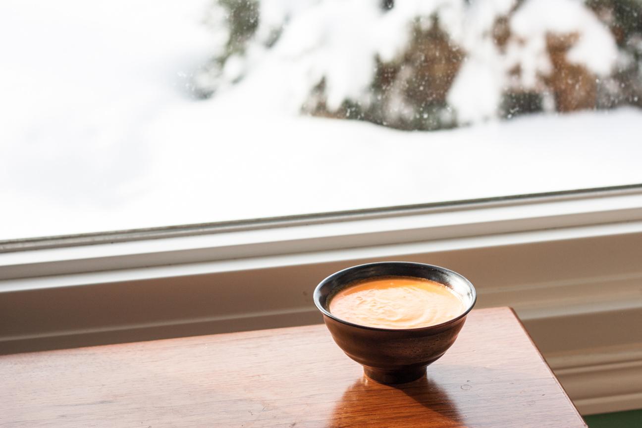carrot lemon soup in bowl near window