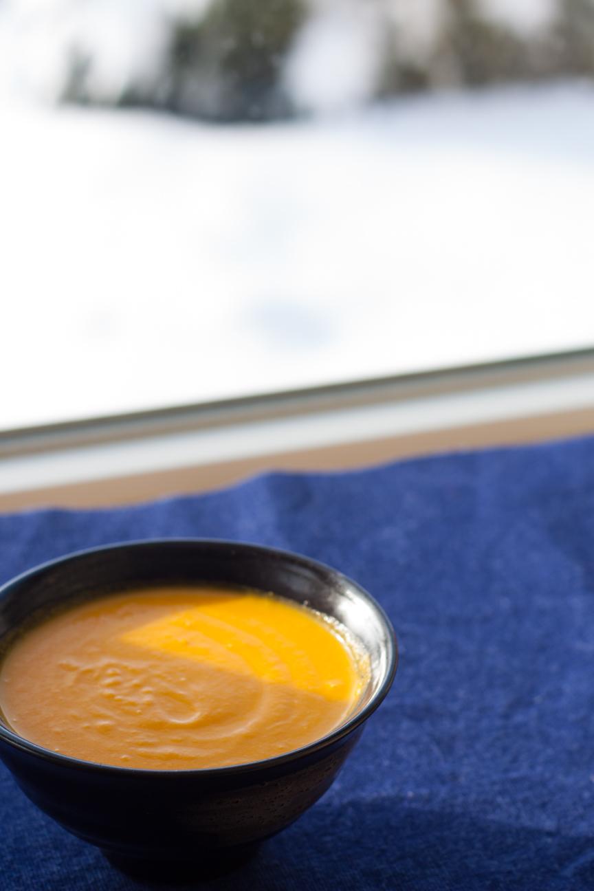 carrot lemon soup in bowl on blue napkin