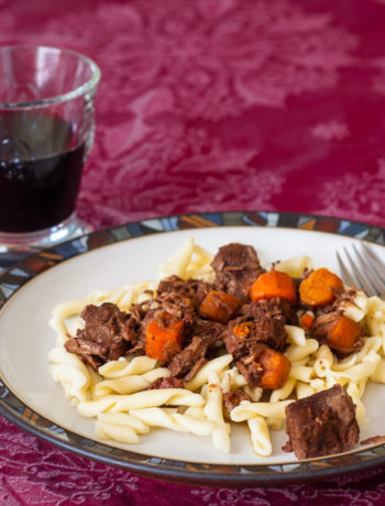 beef stew on plate with glass of red wine