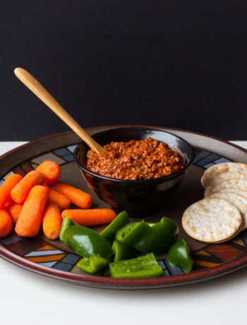 muhammara dip with vegetables and crackers on a platter