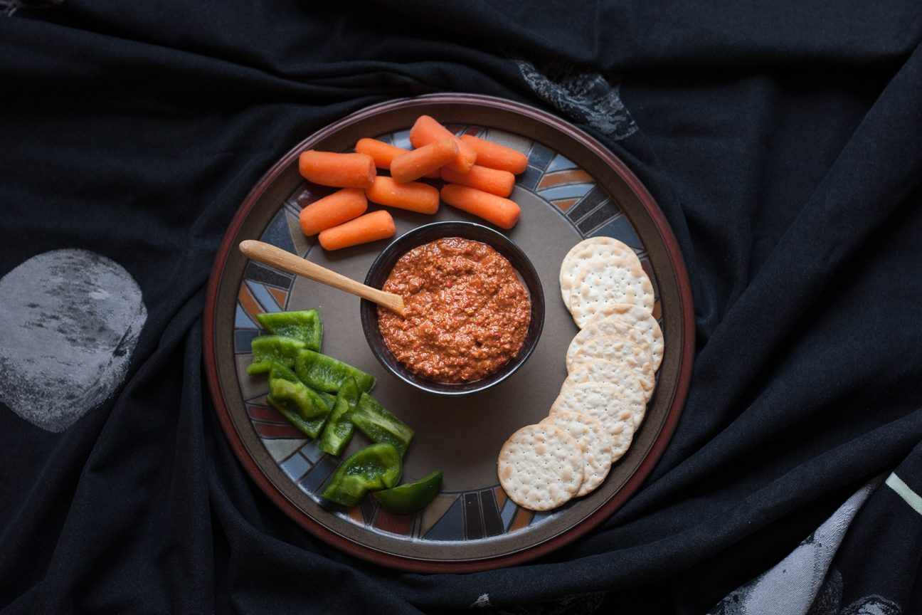 muhammara dip with raw vegetables on a plate