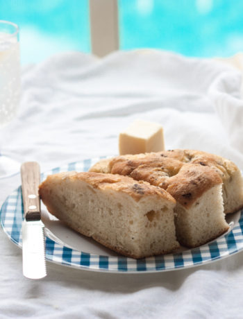 Focaccia Bread with sea salt and black pepper on a plate with butter and knife and drink