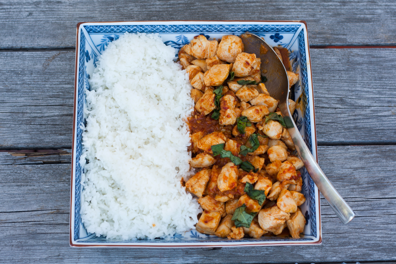 thai chicken with chilies and basil with rice on a plate