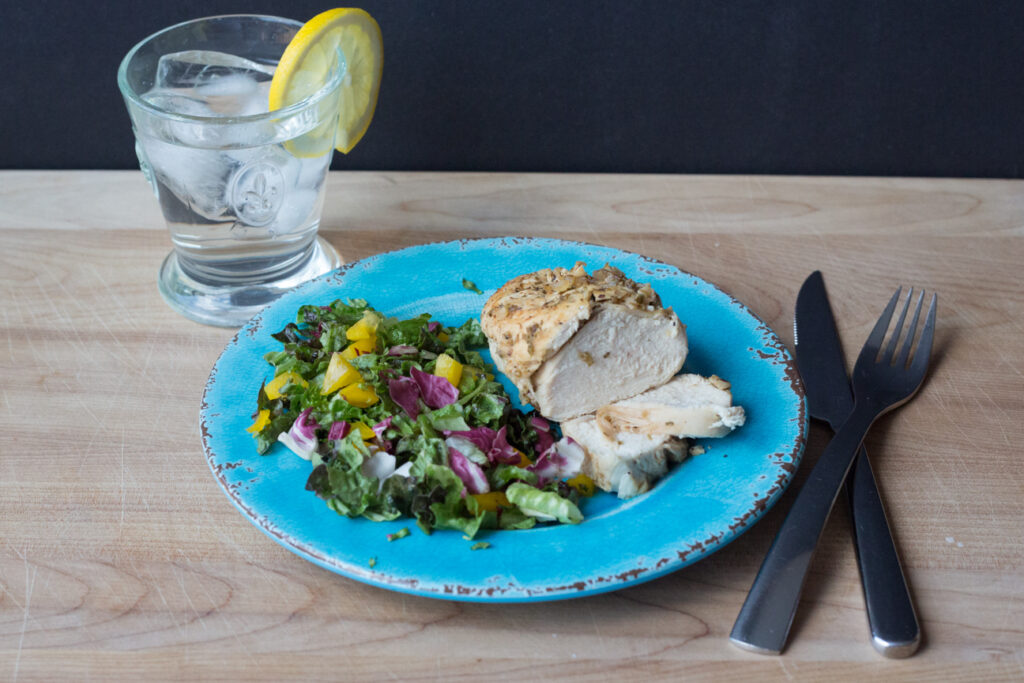 chicken and salad on a blue plate with a glass of water