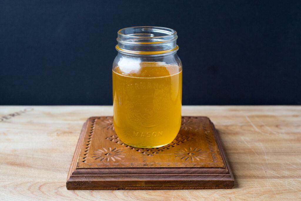 a jar of ghee on a wooden trivet