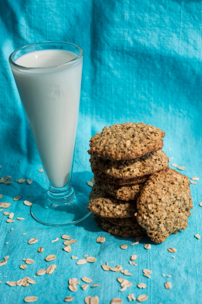 a stack of oatmeal cookies with a glass of milk